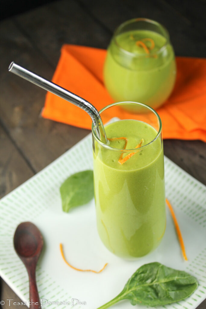 a green orange smoothie in a clear glass with orange zest