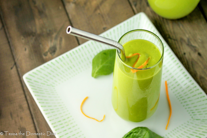 a tall thin clear glass filled with vibrant green smoothie topped with orange zest on white plate
