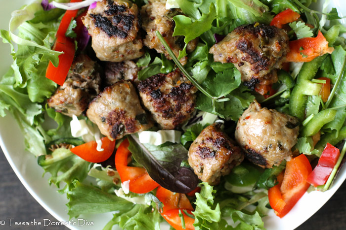 a white bowl filled with leafy greens, peppers, cilantro, cucumber, and pork meatballs