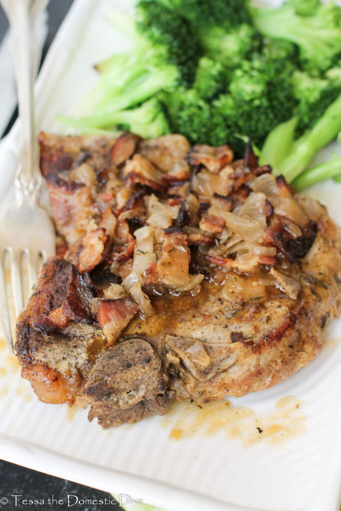 close up view of a single pressure cooker pork chop topped with bacon and gravy.