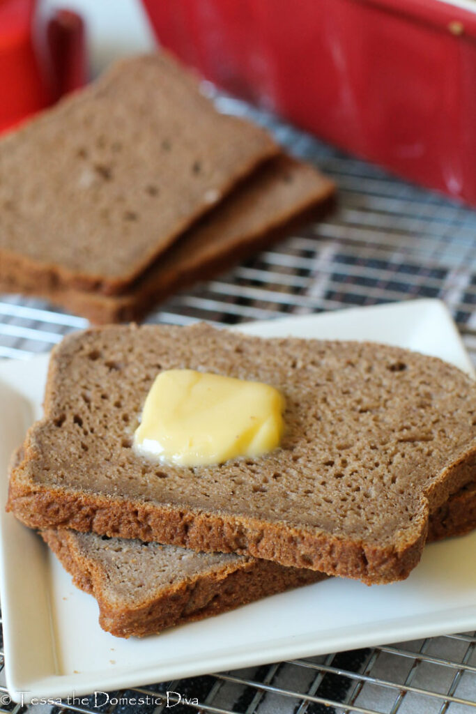 front view of two slices of wholesome gluten free bread with fresh butter on a white plate.